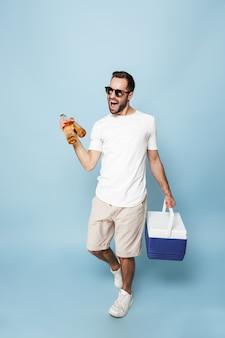 Volledige lengte van een vrolijke opgewonden man met een leeg t-shirt dat geïsoleerd staat over een blauwe muur, met een koeler met koud bier