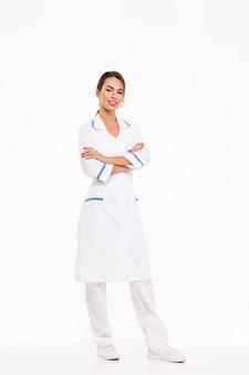 Volledige lengte van een zelfverzekerde jonge vrouw arts die eenvormige status draagt die over witte muur, gevouwen wapens wordt geïsoleerd