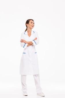 Volledige lengte van een zelfverzekerde jonge vrouw arts die eenvormige status draagt die over witte muur wordt geïsoleerd