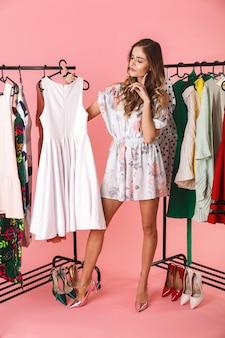 Volledige lengte van elegante vrouw in jurk staande in de buurt van garderobe met kleren en kiezen wat te dragen geïsoleerd op roze