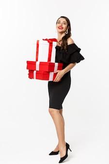 Volledige lengte van elegante vrouw in zwarte jurk, rode lippen, met kerstcadeautjes en glimlachend blij, geschenken ontvangen, staande op witte achtergrond.