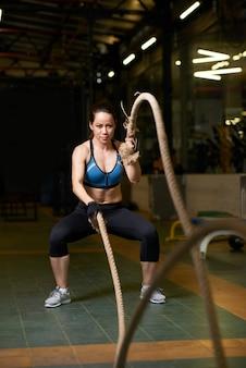 Volledige lengte van fit meisje doet crossfit oefening