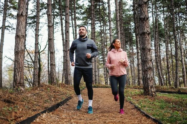 Volledige lengte van fit paar loopt door bos in de herfst en voorbereiden op marathon
