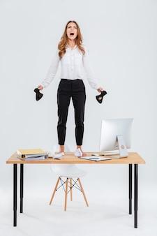 Volledige lengte van gekke jonge zakenvrouw die op tafel staat en over witte achtergrond schreeuwt