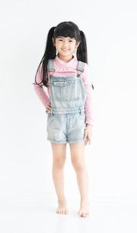 Volledige lengte van gelukkig en grappig gezicht expressie aziatisch klein kind meisje jurk in casual staande in witte kamer.