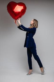 Volledige lengte van gelukkige dame in pak die hartvormige ballon houdt en ernaar kijkt, geïsoleerd op grijze muur