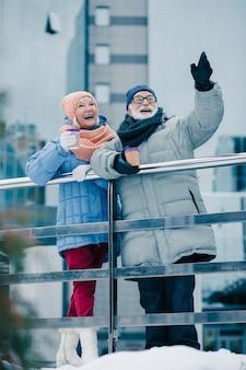 Volledige lengte van gelukkige paar gepensioneerden in winterkleren met koffie om te gaan en weg te kijken met een glimlach. man die één hand opsteekt