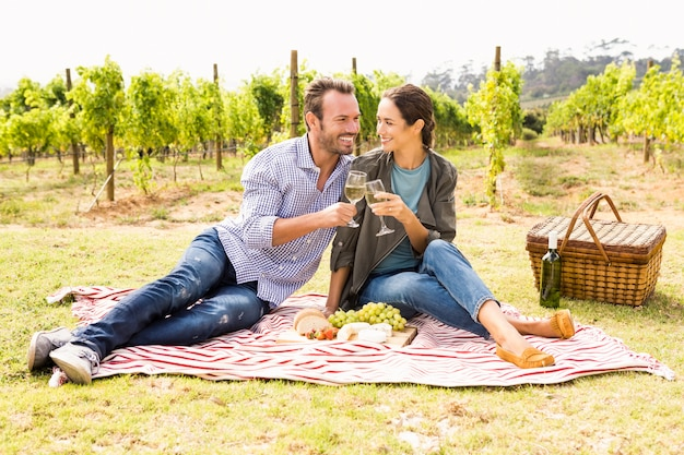 Volledige lengte van gelukkige paar roosterende wijnglazen