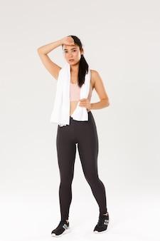 Volledige lengte van gemotiveerde, vermoeide vrouwelijke atleet, aziatisch fitnessmeisje met handdoek, zweet afvegen tijdens training trainingssessie, sportschool bijwonen, oefeningen doen.