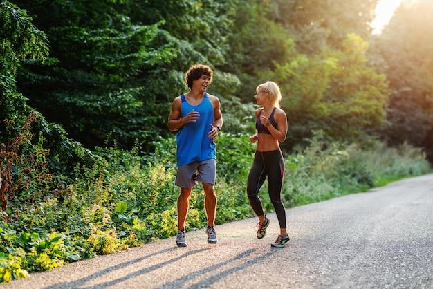 Volledige lengte van glimlachend kaukasisch paar dat in aard op zonnige de zomerdag loopt.