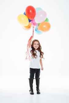 Volledige lengte van glimlachend meisje dat kleurrijke ballons houdt