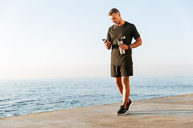 Volledige lengte van glimlachende sportman die mobiele telefoon met behulp van