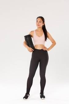 Volledige lengte van glimlachende zelfverzekerde en gemotiveerde aziatische vrouwelijke gymnastiekcoach, fitnessmeisje in sportkleding, tevreden rondkijken, schuimroller vasthouden om te gebruiken na training, staand met trainingsapparatuur.