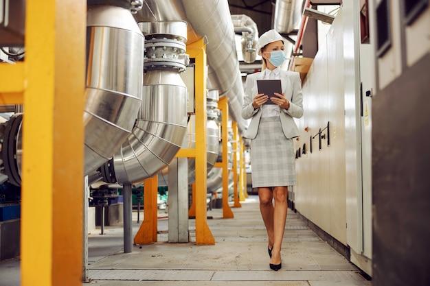 Volledige lengte van hardwerkende blonde vrouwelijke supervisor in pak met helm en gezichtsmasker op tablet vasthouden en rondlopen verwarmingsinstallatie tijdens uitbraak coronavirus.