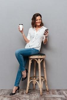 Volledige lengte van het glimlachen vrouw stellen op stoel met in hand kop van koffie en het gebruiken van smartphone op grijs