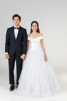 Volledige lengte van jong aantrekkelijk aziatisch paar, spoedig bruid en bruidegom, vrouw die witte huwelijkstoga draagt. man met zwarte smoking, staande samen. concept voor pre-huwelijksfotografie.