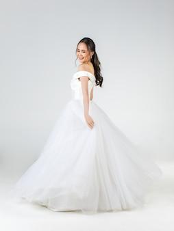 Volledige lengte van jonge aantrekkelijke aziatische vrouw, binnenkort bruid, gekleed in een witte trouwjurk die er gelukkig uitziet. concept voor pre-huwelijksfotografie.