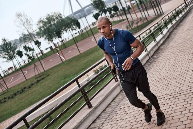 Volledige lengte van jonge actieve afrikaanse man met koptelefoon die buiten jogt jogging