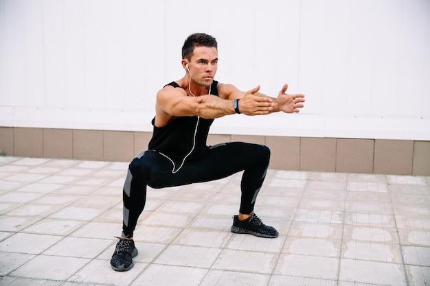 Volledige lengte van jonge geconcentreerde sportman die hurkzit doen tijdens training in openlucht