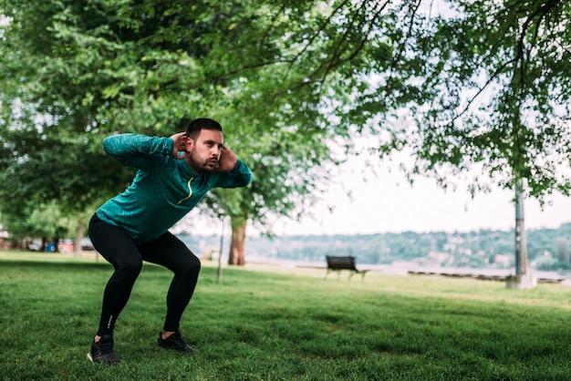 Volledige lengte van jonge geconcentreerde sportman die squats in openlucht doet.
