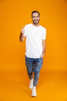 Volledige lengte van jonge kerel in t-shirt en spijkerbroek die duim toont terwijl hij staat, geïsoleerd op geel