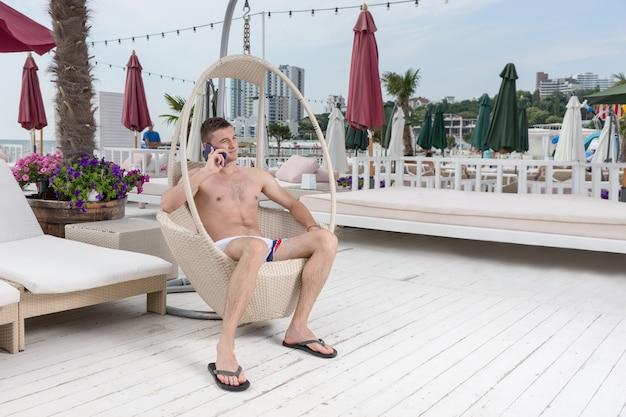Volledige lengte van jonge man in badpak bellen op mobiele telefoon terwijl u ontspant in rieten ligstoel op terras van oceanfront luxe vakantieresort
