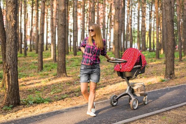 Volledige lengte van jonge moeder met een kinderwagen in het park