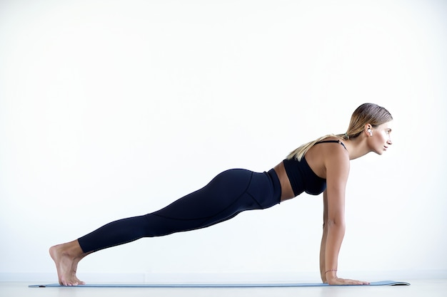 Volledige lengte van jonge mooie vrouw in sportkleding plank doen en haar kernspieren werken op sportschool.
