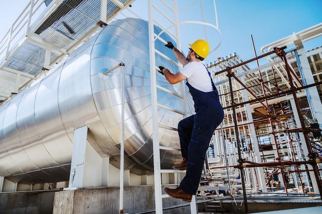 Volledige lengte van kaukasische hardwerkende werknemer klimmen op olietank. buitenkant van de raffinaderij.