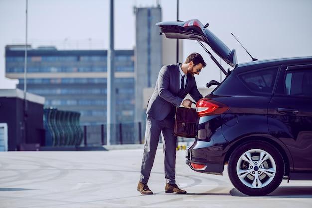 Volledige lengte van knappe blanke bebaarde zakenman met zonnebril zijn lederen tas uit de kofferbak te nemen.