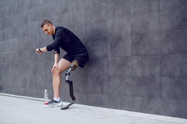 Volledige lengte van knappe blanke sportman met kunstbeen leunend op de muur, polshorloge kijken en rusten van hardlopen. naast hem staat een fles met verfrissing.