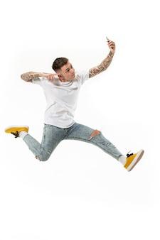 Volledige lengte van knappe jonge man die telefoon neemt terwijl hij tegen oranje studioachtergrond springt.