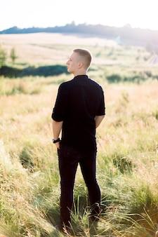 Volledige lengte van knappe jonge man in zwart shirt en broek, permanent buiten in het prachtige groene zomer veld bij zonsondergang
