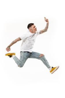 Volledige lengte van knappe jonge man selfie te nemen tijdens het springen