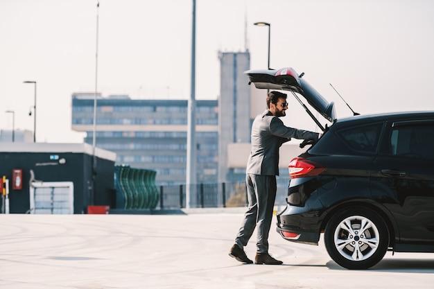 Volledige lengte van knappe kaukasische bebaarde rijke zakenman in pak kofferbak op zijn auto openen en zijn aktetas erin zetten.