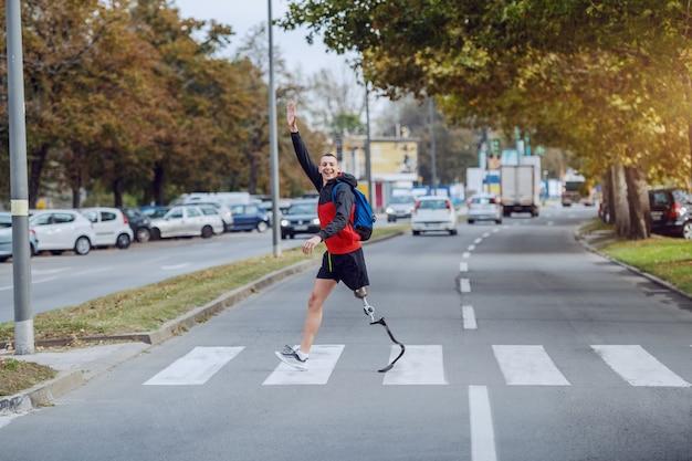 Volledige lengte van knappe kaukasische gehandicapte sportman in sportkleding, met kunstbeen en rugzak die straat oversteken en naar een vriend zwaaien.