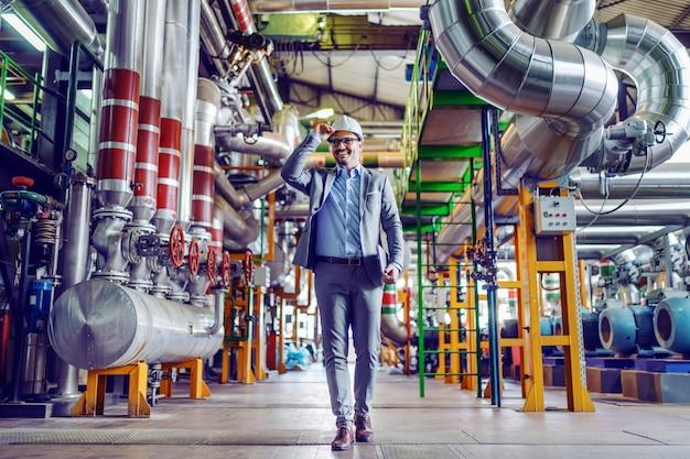 Volledige lengte van knappe kaukasische supervisor in kostuum en met helm op hoofdholdingstablet in handen en het lopen. elektriciteitscentrale interieur.