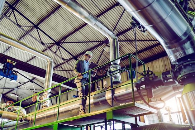 Volledige lengte van knappe kaukasische supervisor in pak en met helm met behulp van tablet terwijl leunend op reling. elektriciteitscentrale interieur.