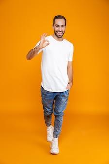 Volledige lengte van knappe kerel in t-shirt en spijkerbroek die ok teken toont terwijl hij staat, geïsoleerd op geel