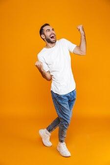 Volledige lengte van knappe kerel in t-shirt en spijkerbroek die vuisten balde terwijl hij staat, geïsoleerd op geel
