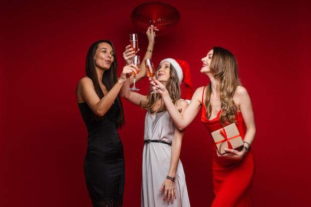 Volledige lengte van lachende mooie drie vriendinnen rammelende glazen met champagne, geïsoleerd op rode muur
