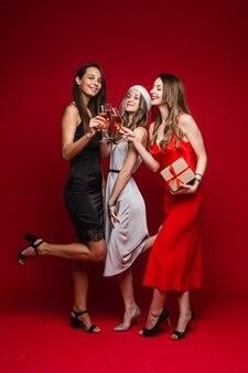 Volledige lengte van lachende mooie drie vriendinnen rammelende glazen met champagne, op rood.