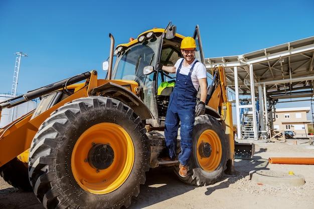 Volledige lengte van lachende positieve hardwerkende werkman in overall en met helm op hoofd verlaten graafmachine. buitenkant van de raffinaderij.