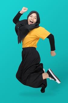Volledige lengte van leuk aziatisch tienermeisje die hoofddoek dragen die op blauw springt