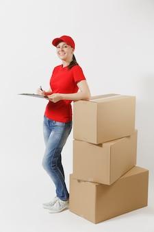 Volledige lengte van levering vrouw in rode dop, t-shirt geïsoleerd op een witte achtergrond. vrouwelijke koerier met klembord met papieren document, leeg leeg vel op lege kartonnen dozen. pakket ontvangen.