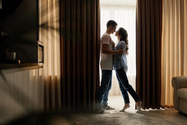 Volledige lengte van liefdevolle paar knuffelen in keuken thuis terwijl we kijken naar elkaar tegen het raam. relatie, liefde concept. low key.