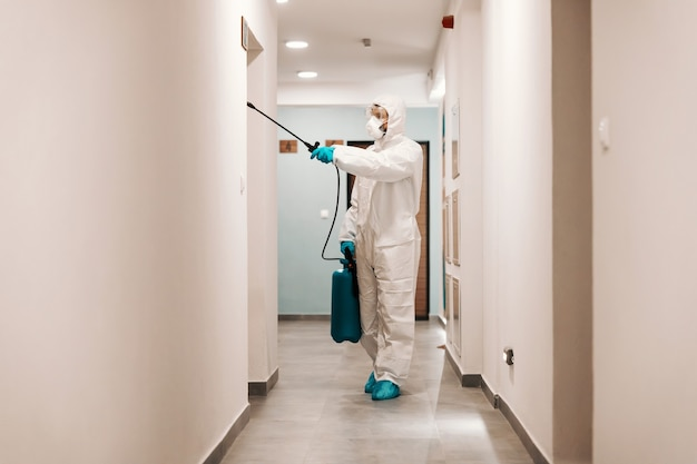 Volledige lengte van man in steriel pak die hal van het gebouw desinfecteert. bescherming tegen corona-concept.