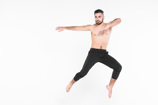 Volledige lengte van mensenballetdanser die in medio lucht springt die op wit wordt geïsoleerd