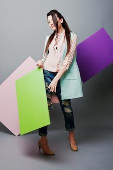 Volledige lengte van mooi meisje, met groen leeg reclamebord, over grijze achtergrond en roze en violette banner