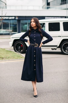 Volledige lengte van mooie brunette jonge vrouw in lange donkere jurk